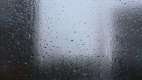 Regnen Sie, großer Regentropfenstreik ein Fenster während a