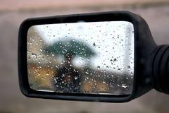 Regnen Sie Spiegel und Regenschirm stockfoto