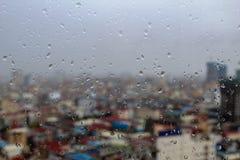 Regnen Sie Tröpfchen auf einem Fenster mit einer Stadtansicht Stockfotos