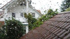 Regnen Sie Tropfen auf Fensterglas mit Ansicht zum Nachbarhaus stock video