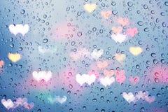 Regnen Sie Tropfen auf Glas mit abstrakten Herzlichtern Lizenzfreie Stockbilder