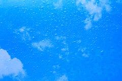 Regnen Sie Tropfen auf Glas mit Wolke des blauen Himmels Stockbild