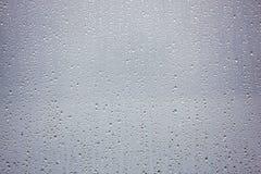 Regnen Sie Tropfen auf Glasfenster an einem dunklen stürmischen Nachmittag Lizenzfreie Stockfotos