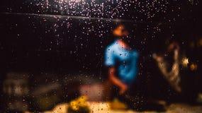 Regnen Sie Tropfen auf Glasfenster und dem Mann, die Materialien verkauft Stockfotos