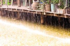 Regnen Sie Tropfen des Wassers mit hölzernem Haus der Weinlese auf Kanal stockbild
