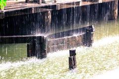 Regnen Sie Tropfen des Wassers mit hölzernem Haus der Weinlese auf Kanal lizenzfreies stockfoto