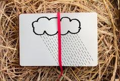 Regnen Sie Zeichnung auf Skizzenbuch im Heukastenhintergrund Stockbild