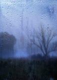 Regnerische Herbstlandschaft durch ein Fenster mit Regentropfen Lizenzfreie Stockfotografie