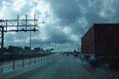 Regnerische treibende Straße Miamis Florida mit LKWs Lizenzfreies Stockbild
