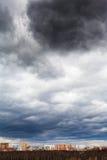 Regnerische Wolken des dunkelgrauen Sturms unter Stadt Stockfotografie