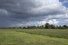 Regnerischer bewölkter Himmel mit einer niederländischen Windmühle und einer Eisenbahnbrücke herein lizenzfreie stockbilder