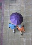 Regnerischer Frühling und ältere Paare mit einem Regenschirm, der auf einen Bürgersteig geht Lizenzfreie Stockfotos