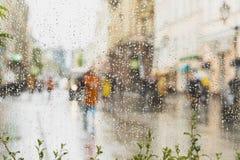 Regnerischer Tag in der Stadt Leute gesehen durch Regentropfen auf Glas Selektiver Fokus auf den Regentropfen Lizenzfreies Stockfoto
