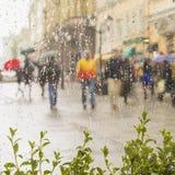 Regnerischer Tag in der Stadt Leute mit dem Regenschirm gesehen durch Regentropfen auf Glas des Fensters Selektiver Fokus auf den Stockfotografie