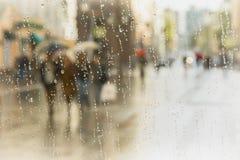 Regnerischer Tag in der Stadt Schattenbild von Leuten mit dem Regenschirm gesehen durch Regentropfen auf Glas des Fensters Selekt Stockbild