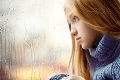 Regnerischer Tag: Mädchen, das durch das Fenster schaut Stockbilder