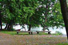 Regnerischer Tag an Trakai-Naturpark, eine Ansicht zu einem See, alte große Bäume, Holzbanken und ein Fischerboot Stockbild
