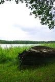 Regnerischer Tag an Trakai-Naturpark, eine Ansicht zu leicht geschlagen über altem großem hölzernem Boot, ein See und ein Wald Stockbild