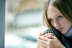 Regnerischer Tag: trauriges Mädchen auf dem Fenster Stockbilder