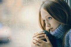 Regnerischer Tag: trauriges Mädchen auf dem Fenster Lizenzfreie Stockbilder