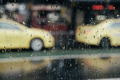 Regnerisches Fenster mit den Taxiautos verwischt im Hintergrund lizenzfreie stockfotos