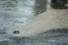 Regnerisches Wetter Hochwasser, der in Abwasserkanal fließt stockbilder