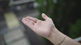 Regnerisches Wetter, Regentropfen, die auf die Hand der Frau fallen Regen f?llt auf eine Mann ` s Hand stock video