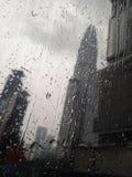 Regnig dag droppar på fönsterexponeringsglaset, cityview arkivfoton
