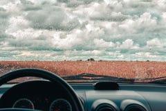 Regnig dag i bilfönstret Vetefält efter regn Mulet väder och molnig himmel Royaltyfri Fotografi