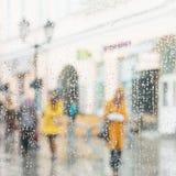 Regnig dag i stad Folk som ses till och med regndroppar av fönstret Selektiv fokus på regndroppar Konturer av flickor i ljust Arkivfoton