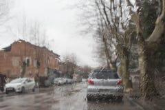 Regnig dag i staden, trafiken och bilnad-dropparna av regn på bilvindrutan arkivbild