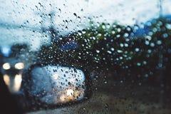Regnig dag på vägen, regndroppar på bilspegeln med sidovingspegeln Arkivbild