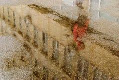 regnig dag Reflexion i pöl på stadsgatan under regn Royaltyfria Bilder