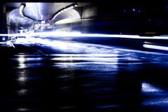 Regnig natttrafik framme av tunnelen royaltyfria foton