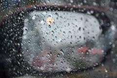 Regniga dagar regn tappar på ett bilfönster Arkivbilder