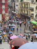 regniga paraplyer för dagmacau folk under Arkivbilder