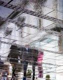 Regniga reflexioner av folk på stadsgatan som är uppochnervända Arkivbilder
