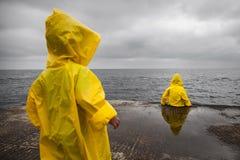 Regnigt molnigt väder Två barn i gula regnrockar royaltyfria foton