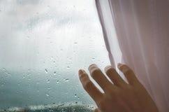 Regnigt väder - en hand för kvinna` s drar rullgardinen från det regniga fönstret arkivbilder