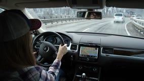 regnigt väder Flickan kör en bil Bilen flyttar sig på bron Torkarearbete Ögon är synliga i spegeln 4K lager videofilmer