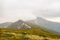 Regnmoln som hägrar i Carpathiansna för regnet och hagelet På lutningarna av snö Royaltyfri Foto
