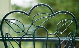 Regnsmå droppar på grön stol arkivfoton
