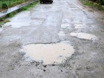Regnvatten fyllda krukahål på grusvägen Royaltyfri Foto