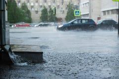 Regnvatten som flödar från en metalldownspout under en hällregn begrepp av skydd mot hällregn och regnfloder Royaltyfri Fotografi