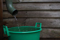 Regnvattenskytte från en avloppsränna in i ett vatten som samlar behållaren Arkivbilder