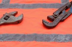 Regolabile e chiavi stringitubo contro lo sfondo di una camicia arancio del lavoratore del segnale Natura morta connessa con la r Immagini Stock Libere da Diritti