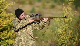 Regolamento di caccia Fucile della tenuta del cacciatore Cacciatore barbuto spendere caccia di svago Fuoco e concentrazione di co immagini stock libere da diritti