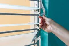 Regolando il vetro e del metallo i ciechi dell'altezza con un metallo si serrano fotografia stock libera da diritti