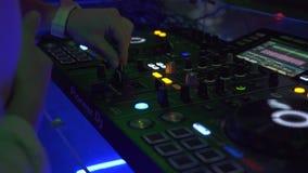 Regolatore del DJ e console di musica alla luce variopinta al partito di ballo in night-club Giocatore del miscelatore del DJ e c stock footage