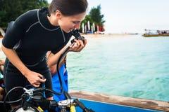 Regolatore di prova dell'operatore subacqueo della donna prima di immersione con bombole Fotografie Stock